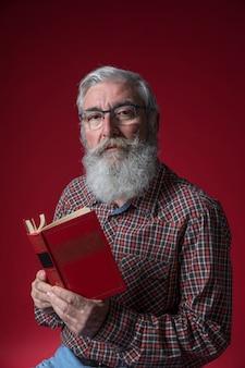 Portret van een hogere mens die met grijze baard aan camera tegen rode achtergrond kijkt