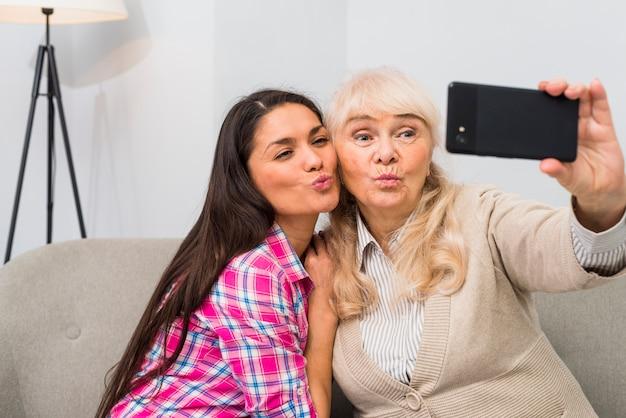 Portret van een hogere moeder en haar volwassen dochter die selfie op slimme telefoon nemen