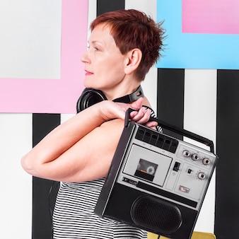 Portret van een hogere vrouw die een uitstekende cassettespeler houdt