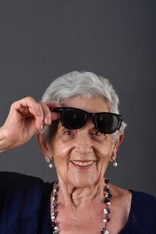 Portret van een hogere vrouw met een bril op het voorhoofd