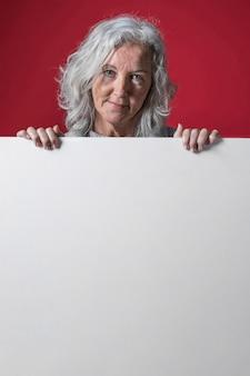 Portret van een hogere vrouw met grijs haar die zich achter het witte aanplakbiljet bevinden tegen rode achtergrond