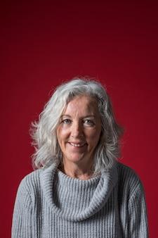 Portret van een hogere vrouw met kort grijs haar tegen rode achtergrond