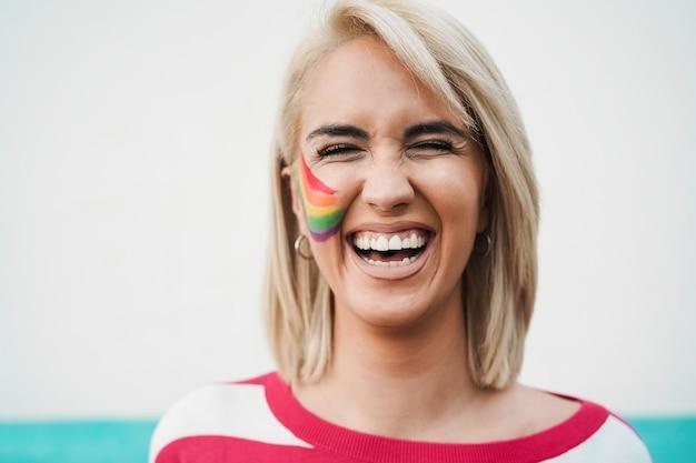 Portret van een homoseksuele vrouw die lacht op de camera tijdens een pride-evenement