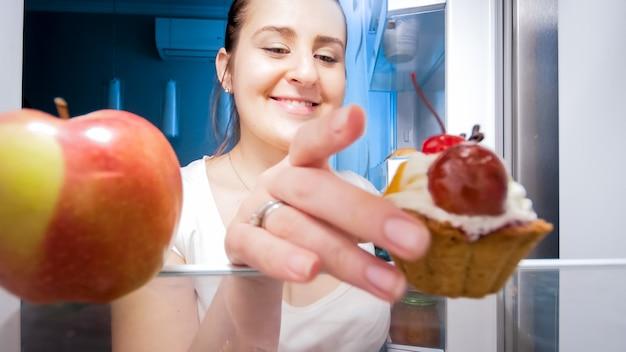 Portret van een hongerige vrouw die zoete cake neemt in plaats van een helthy appel voor een late snack 's nachts. concept van een dieet en gezonde voeding.
