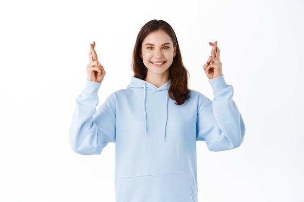 Portret van een hoopvol meisje dat examen wil, kruis vingers veel geluk en kijkt met hoop en positieve glimlach aan de voorkant, droom komt uit, staande tegen een witte muur