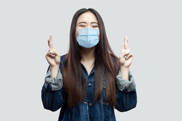 Portret van een hoopvolle brunette aziatische jonge vrouw met een chirurgisch medisch masker in een blauw spijkerjasje dat met gekruiste vinger staat en bidt om te winnen. indoor studio opname, geïsoleerd op een grijze achtergrond.