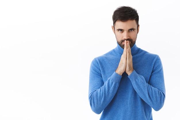 Portret van een hoopvolle knappe slimme man, iets intrigerend, een interessant idee, hand in hand in gebed, wachtend op smaak, er zelfverzekerd uitzien, op een witte muur staan