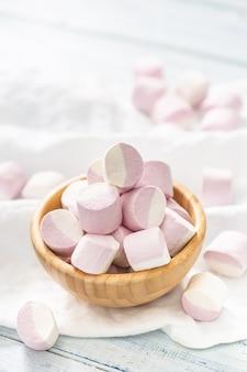 Portret van een houten kom vol roze en witte marshmallows met enkele verspreid op een wit tafelkleed.