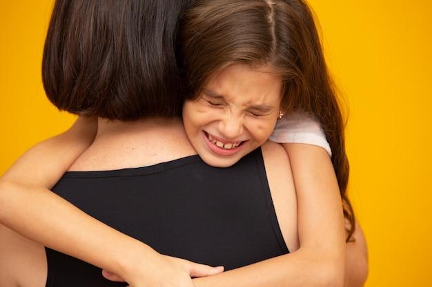 Portret van een huilend meisje dat door haar moeder wordt vastgehouden