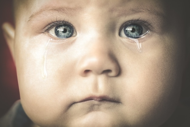 Portret van een huilende kleine baby met blauwe ogen close-up