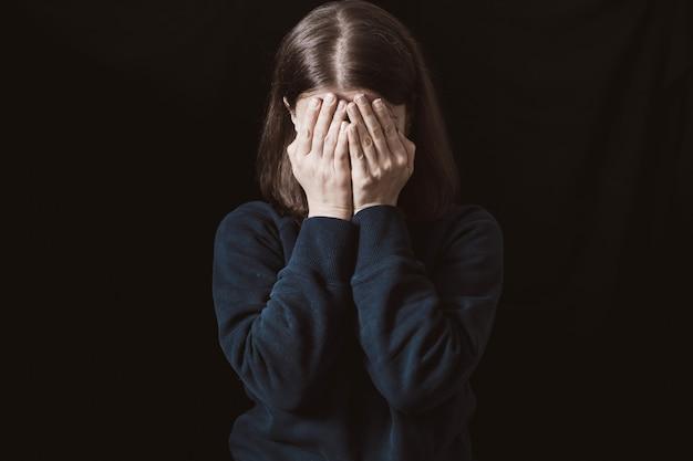 Portret van een huilende vrouw die haar gezicht bedekt met handen. geweld in het gezin. verdriet en depressieve toestand van het meisje.
