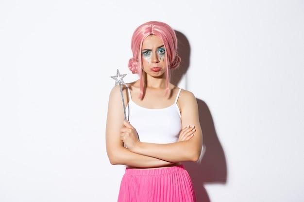 Portret van een humeurig schattig meisje met een roze pruik, gekleed als een fee voor halloween, boos of teleurgesteld, staande op een witte achtergrond