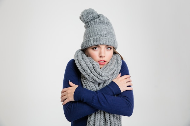 Portret van een ijskoude vrouw in winterdoek staande geïsoleerd op een witte achtergrond