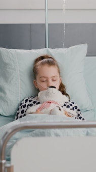 Portret van een in het ziekenhuis opgenomen ziek kind dat in slaap valt terwijl hij een teddybeer in zijn handen houdt