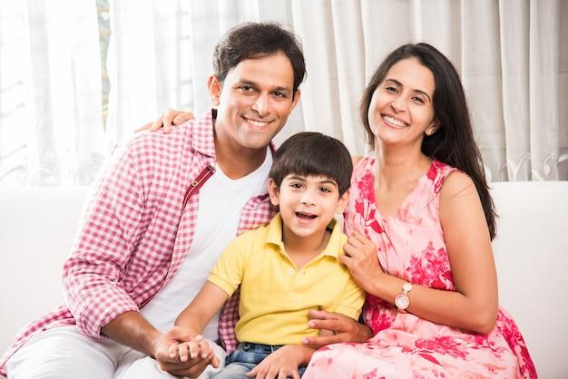 Portret van een indiase aziatische gelukkige en jonge familie, die thuis op de bank zit