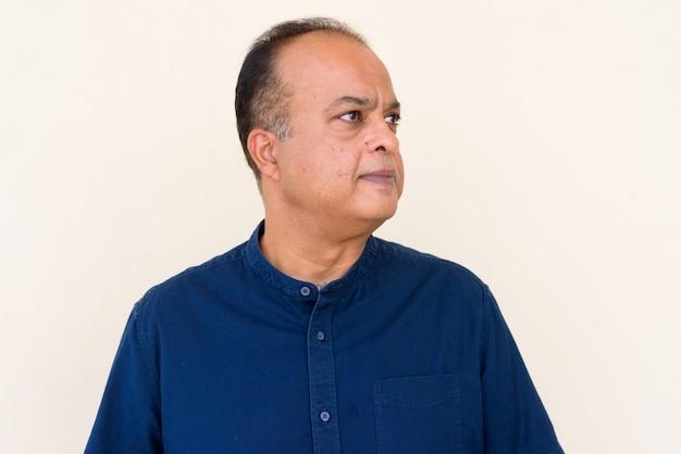 Portret van een indiase man die buiten tegen een gewone muur denkt