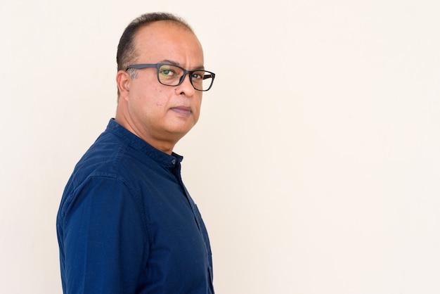 Portret van een indiase man tegen een gewone muur die buiten naar de camera kijkt