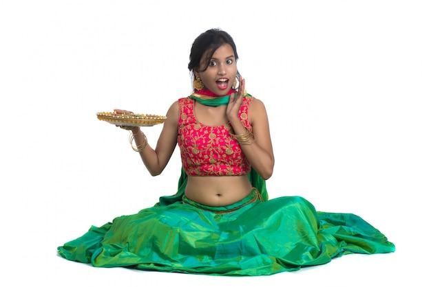 Portret van een indiase traditionele meisje met diya, meisje viert diwali of deepavali met olielamp tijdens festival van licht op wit oppervlak
