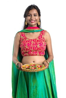 Portret van een indiase traditionele meisje met diya, meisje viert diwali of deepavali met olielamp tijdens festival van licht op witte achtergrond