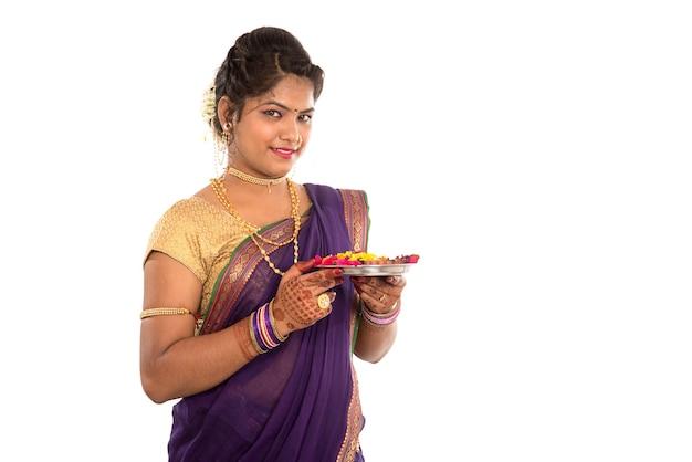 Portret van een indiase traditionele vrouw met pooja thali met diya, diwali of deepavali foto met vrouwelijke handen met olielamp tijdens festival van licht