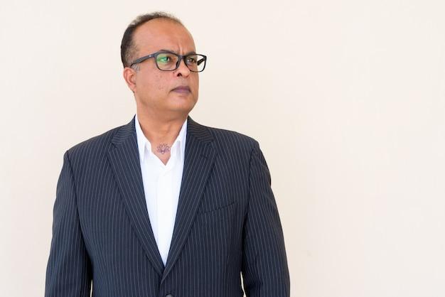 Portret van een indiase zakenman die buiten tegen een gewone muur denkt