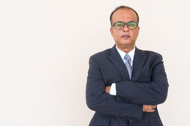 Portret van een indiase zakenman met gekruiste armen buiten tegen een effen muur
