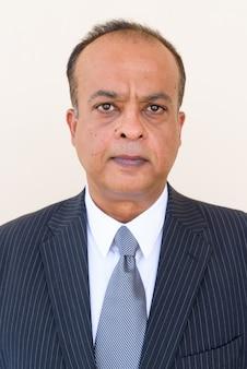 Portret van een indiase zakenman tegen een gewone muur die buiten naar de camera kijkt