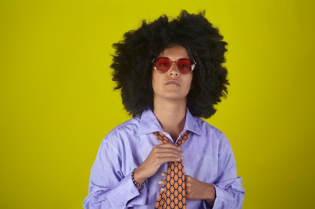 Portret van een indisch meisje met afro krullend kapsel en mannelijke kleren die een gelijkspel op gele muur rechtmaken