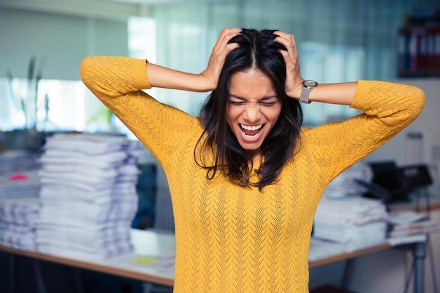 Portret van een informele zakenvrouw die haar oren bedekt en schreeuwt op kantoor