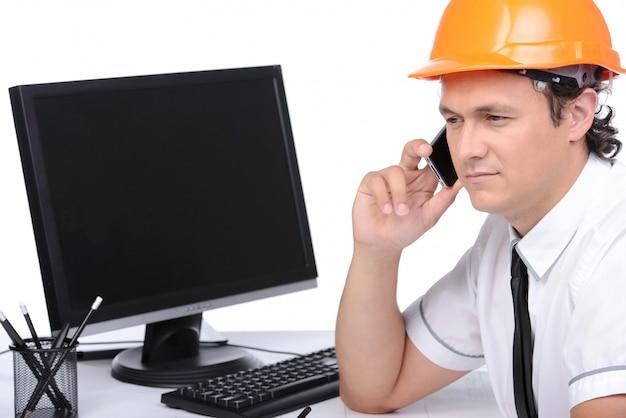 Portret van een ingenieur die een pc gebruikt en aan de telefoon spreekt.