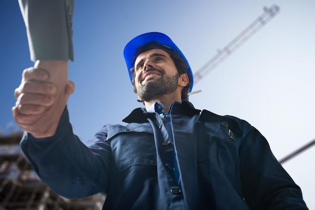 Portret van een ingenieur handen schudden met een klant voor een bouwplaats