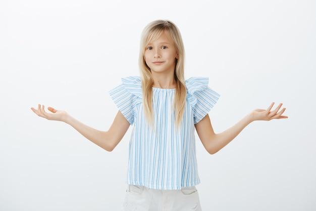Portret van een intens onbewust schattig klein meisje met blond haar, schouderophalend met gespreide handpalmen, lachend met een ongemakkelijke, problematische uitdrukking, niet in staat om te antwoorden, geen idee over grijze muur te staan