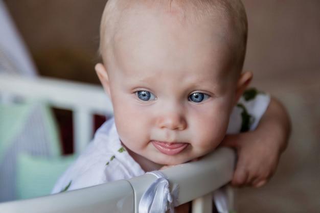 Portret van een jaar oud kind met blauwe ogen kijkt weg in stijlvolle slijtage van wieg. kleine trieste baby met emotie zittend in de kinderkamer en wachtende moeder. concept van goede opvoeding en kindertijd