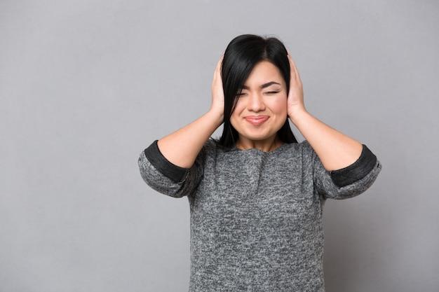 Portret van een japanse vrouw die haar oren behandelt over grijze muur