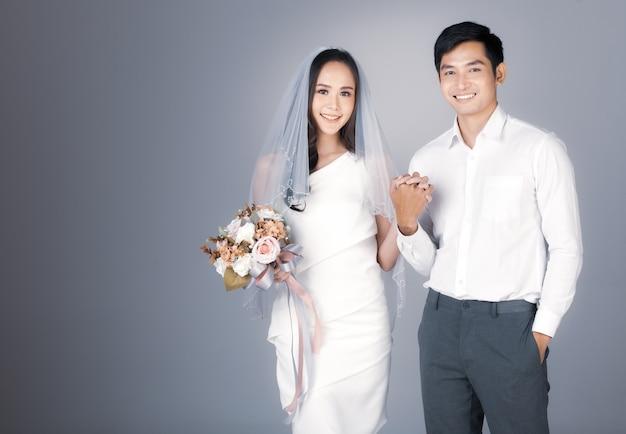 Portret van een jong, aantrekkelijk aziatisch stel dat handen vasthoudt, een man met een wit overhemd, een vrouw die een bruidsjurk draagt met een sluier die een boeket bloemen vasthoudt. concept voor pre-huwelijksfotografie.
