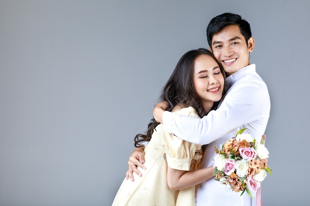 Portret van een jong, aantrekkelijk aziatisch stel, een man met een wit overhemd, een vrouw met een beige jurk die elkaar omhelst, een vrouw met een boeket bloemen. concept voor pre-huwelijksfotografie.