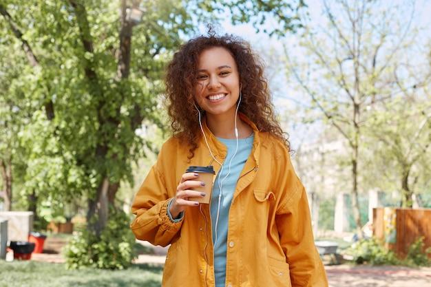 Portret van een jong aantrekkelijk donker krullend meisje dat breed lacht, in het park lopend en genietend van het weer, naar muziek luistert, een kop van koffie houdt, een geel jasje draagt.