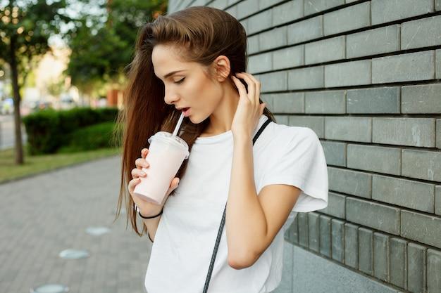 Portret van een jong aantrekkelijk donkerbruin meisje dat milkshake drinkt