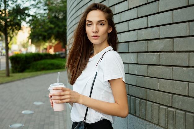 Portret van een jong aantrekkelijk donkerbruin meisje dat milkshake houdt