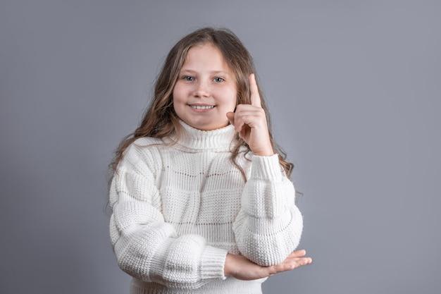 Portret van een jong aantrekkelijk klein meisje met blond haar in een witte trui glimlachend tonen en vinger omhoog, idee op een grijze studio achtergrond. plaats voor tekst.