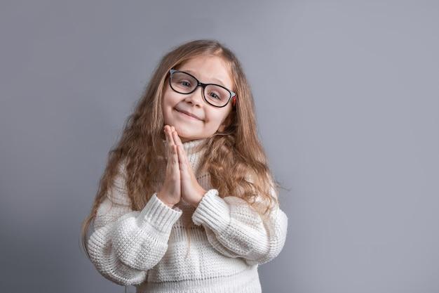 Portret van een jong aantrekkelijk klein meisje met blond lang golvend haar in een witte trui met een glimlach die vraagt, bid op een grijze studioachtergrond. kopieer ruimte.
