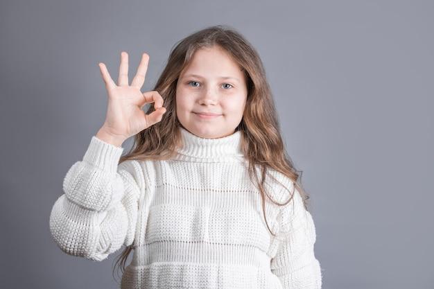 Portret van een jong aantrekkelijk meisje met blond haar in een witte trui glimlachend toont ok teken op een grijze studio achtergrond. plaats voor tekst.