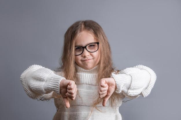 Portret van een jong aantrekkelijk meisje met blond haar in sweater ontevreden scepticus die duimen omlaag afkeer, afkeuringsteken met twee handen op een grijze studioachtergrond toont.