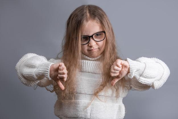 Portret van een jong aantrekkelijk meisje met blond haar in sweater ontevreden scepticus die duimen toont neer houdt niet van
