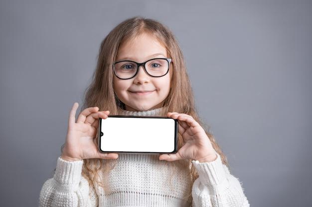 Portret van een jong aantrekkelijk meisje met blond lang golvend haar in een witte sweatergreep toont een mobiele telefoon met een wit leeg scherm op een grijze studioachtergrond. plaats voor tekst. kopieer ruimte.