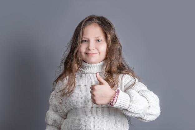Portret van een jong aantrekkelijk meisje met blond lang golvend haar in een witte trui glimlachen duimen opdagen, zoals zingen op een grijze studio achtergrond. plaats voor tekst. kopieer ruimte.