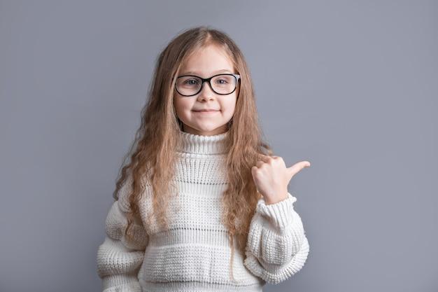 Portret van een jong aantrekkelijk meisje met blond lang golvend haar in een witte trui glimlachend toont zijn handvinger opzij op een grijze studioachtergrond. plaats voor tekst.