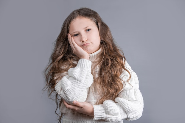 Portret van een jong aantrekkelijk meisje met blond lang stromend haar in een witte sweater die op een grijze studioachtergrond ontevreden is. kopieer ruimte.