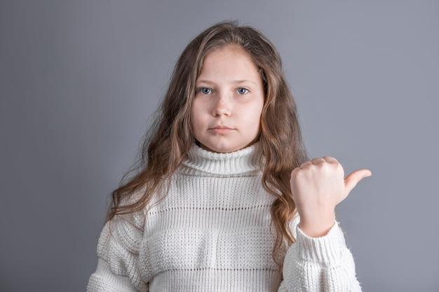 Portret van een jong aantrekkelijk meisje met blond lang stromend haar in een witte trui glimlachen toont zijn hand