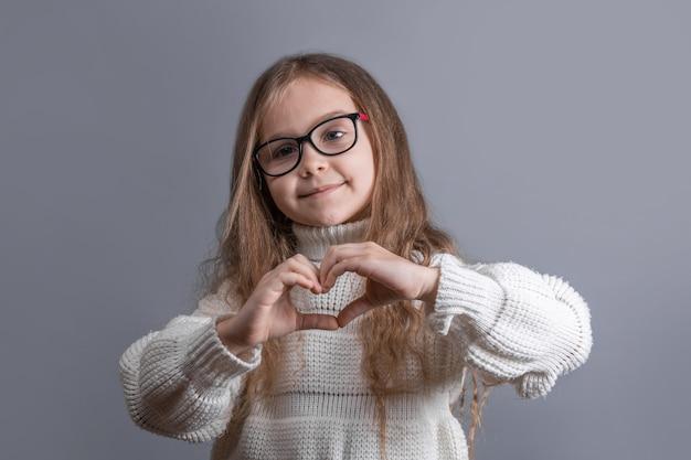 Portret van een jong aantrekkelijk meisje met blond lang stromend haar in een witte trui glimlachend toont hart handen op een grijze studio achtergrond. plaats voor tekst. kopieer ruimte.